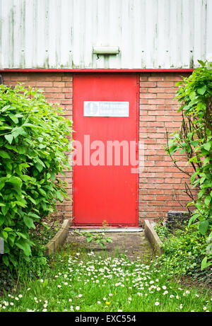 Red door as a fire escape exit in a warehouse in England - Stock Photo