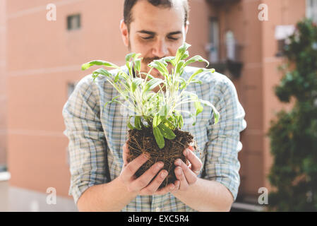 handsome stylish man gardening at home - Stock Photo