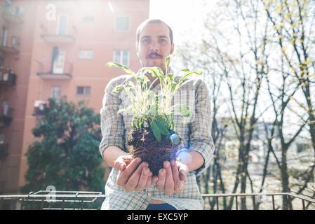 handsome stylish man holding basil plant at home - Stock Photo