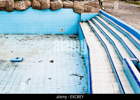 A derelict swimming pool in an abandoned amusement park - Stock Photo
