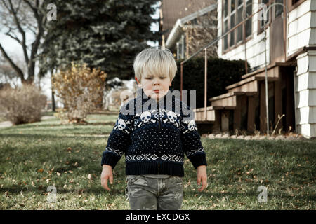 A crabby young blond boy wearing a sweater with skulls stands in the front yard of a house in a neighborhood. - Stock Photo