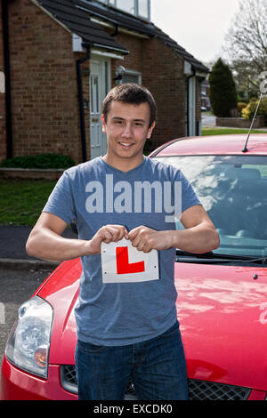 Model released image of a young man who has just passed his driving test and so happy with the result he rips up - Stock Photo
