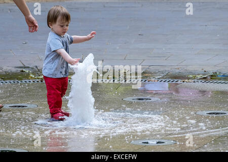 Russell Square Gardens, London, UK. 11th July, 2015.    A toddler escapes the heat in London today by cooling off - Stock Photo