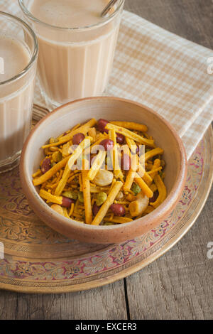 Masala Chai and a bowl of spicy Bombay Mix - Stock Photo