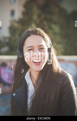 young beautiful long hair woman in town during sunset backlight listening music with headphones - Stock Photo