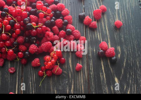 lie on a wooden board red, black currants, raspberries - Stock Photo