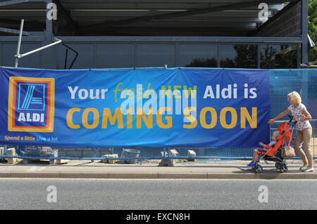 A woman pushing a baby in a pushchair walks past a new Aldi Supermarket being built. Picture: Scott Bairstow/Alamy - Stock Photo