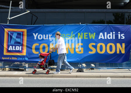 A man pushing a baby in a pushchair walks past a new Aldi Supermarket being built. Picture: Scott Bairstow/Alamy - Stock Photo