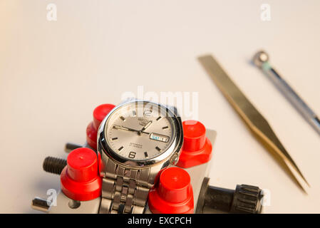 seiko 5 automatic mans wrist watch, set in a watchmakers vice with tools a screwdriver and a pair of tweezers in - Stock Photo