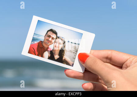Girl Holding Instant Photo Of Young Happy Couple - Stock Photo
