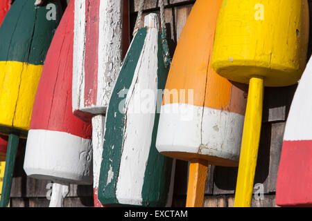Close-up of colorful lobster trap buoys on the cedar shake covered wall of building in Maine. - Stock Photo
