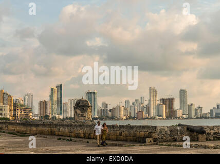A middle-aged couple walking atop the stone wall of the Ciudad Vieja or 'Old City' of Cartagena, Colombia.  The - Stock Photo