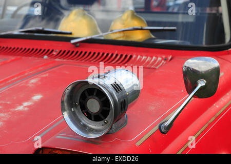 Closeup of old fire truck with a siren on the fender.
