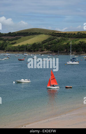 Salcombe, Devon, UK. Small yacht wit red sail on the water at Salcombe in Devon - Stock Photo