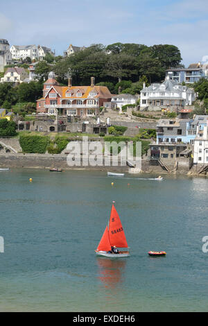 Salcombe, Devon, UK. Small yacht with red sail sailing on the river at Salcombe. - Stock Photo