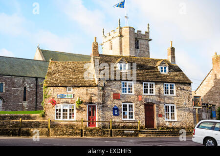 Typical English village square, Corfe in Dorset. Showing village shop with church tower behind. Early morning. - Stock Photo