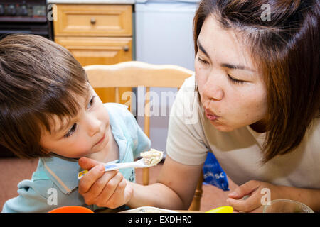 3 to 5 year old Caucasian boy, indoors. Mother and young child sitting and eating dinner, blowing on the food to - Stock Photo