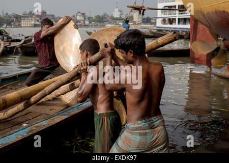 Dhaka, Bangladesh. 12th July, 2015. Laborers pull a propeller into a motor boat. Credit:  Mohammad Ponir Hossain/ZUMA - Stock Photo