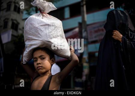 Dhaka, Bangladesh. 12th July, 2015. July 12, 2015 - Dhaka, Bangladesh - Boy carries a bag on his head. © Mohammad - Stock Photo
