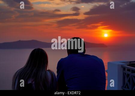 A couple witnessing the sunset on the island of Santorini Greece - Stock Photo