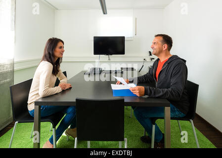 Young female candidate talking during job interview - Stock Photo