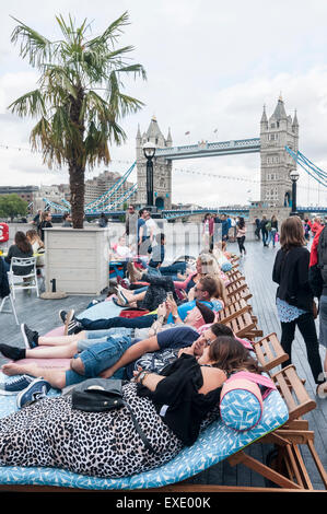 London, UK. 12th July, 2015. UK Weather: Tourists take advantage of the deckchairs and seating amidst the palm trees - Stock Photo