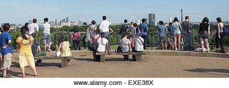View of tourists standing viewing London from the top of Primrose Hill viewing on a summer day - Stock Photo