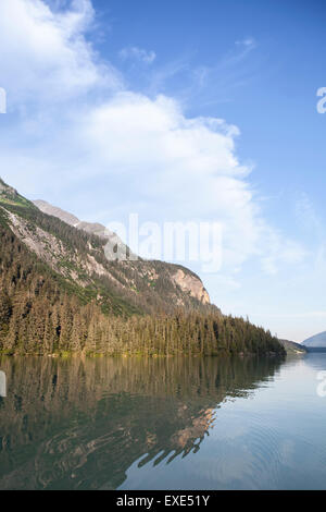 Chilkooot Lake with mountains in Southeast Alaska in summer evening light with clouds and reflections. - Stock Photo