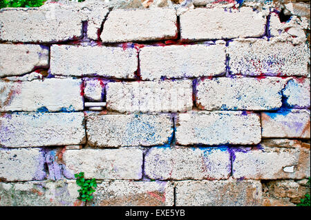 Brick wall with colorful paint marks - Stock Photo