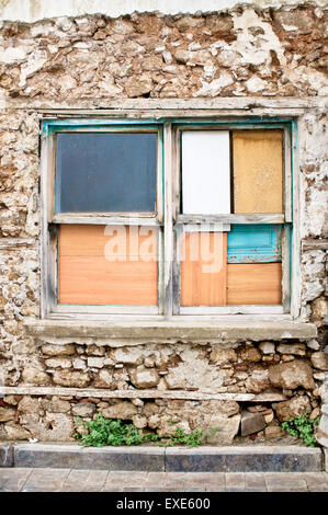 A window boarded up by wooden panels in an old house - Stock Photo