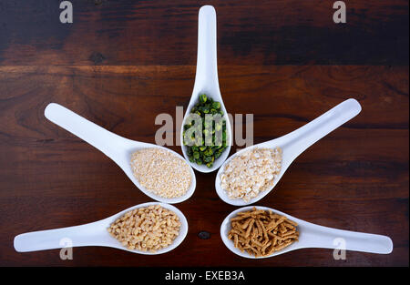 Healthy High Fiber Prebiotic Grains in serving spoons, including wheat bran cereal, oat flakes, dried legume peas, - Stock Photo