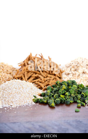 Stack of Healthy High Fiber Prebiotic Grains including wheat bran cereal, oat flakes and pearl barley, on rustic - Stock Photo