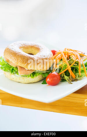 smoked salmon and cream cheese bagel with salad - Stock Photo