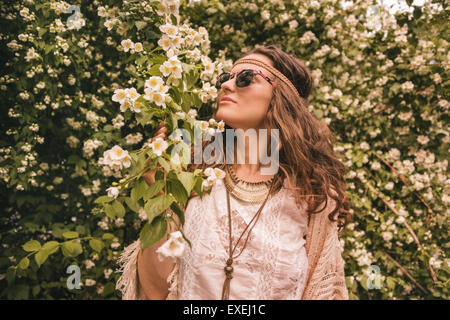 Longhaired hippy-looking young lady in knitted shawl and white blouse enjoying flowers fragrance - Stock Photo