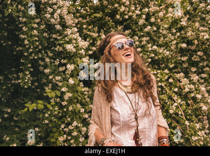 Longhaired hippy-looking young lady in knitted shawl and white blouse standing among flowers and looking up on copy - Stock Photo