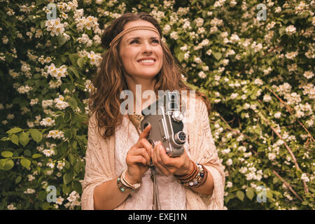 Longhaired hippy-looking young lady in knitted shawl and white blouse standing among flowers with retro camera - Stock Photo