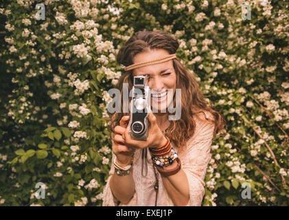 Longhaired hippy-looking young lady in knitted shawl and white blouse standing among flowers playing with retro - Stock Photo