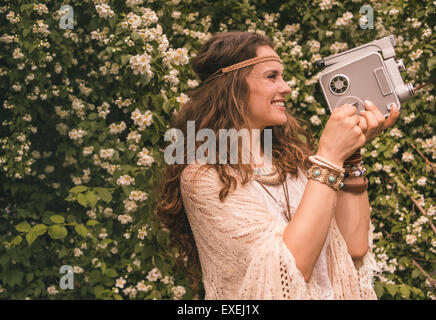 Longhaired hippy-looking young lady in knitted shawl and white blouse standing among flowers and using retro camera - Stock Photo