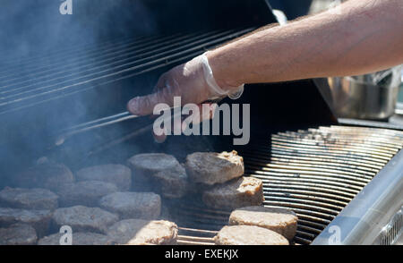 cooking steaks on a hot grill in a summer day - Stock Photo
