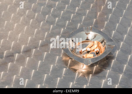 Stubbed out cigarette ends filters cigarettes in a stainless steel ashtray outdoors on a metal table. Smoking concept - Stock Photo