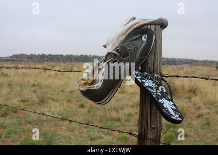 Shoes nailed to a fence post by the side of Route 66 in New Mexico USA - Stock Photo