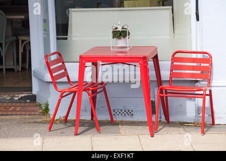 two chairs and a table on the pavement outside a cafe with a sash