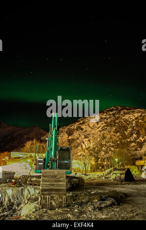 work site at night with excavator, mountain and Aurora Borealis (Northern Lights) - Stock Photo