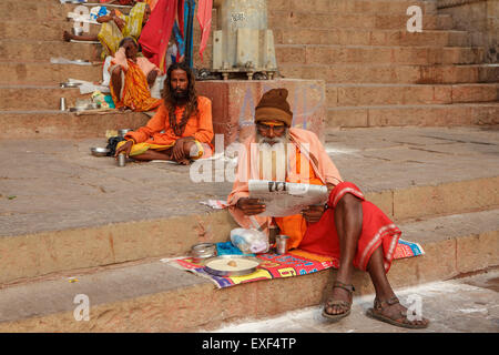 Sadhu ,whit-in his traditional dress, comfortably sits and reads Indian newspaper - Stock Photo
