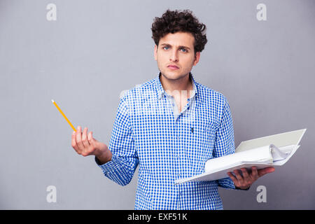 Young serious man holding pencil and folder with files over gray background. Looking at camera - Stock Photo