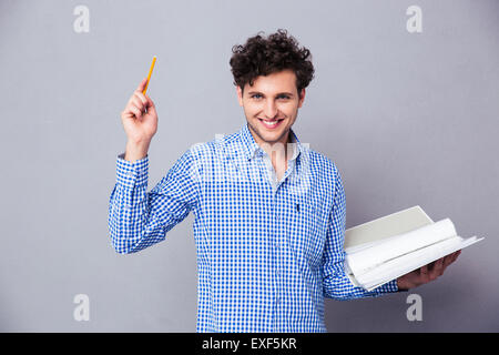 Happy casual man holding pencil and folder with files over gray background. Looking at camera - Stock Photo