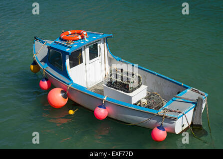 Small fishing boat in Portreath harbour with two creel shape lobster pots, Cornwall England. Stock Photo