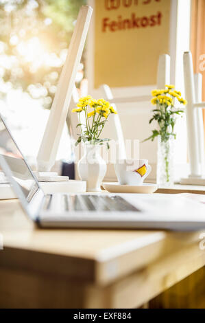 Laptop on table in cafe with coffee cup beside it - Stock Photo