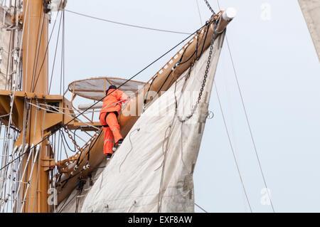 Sailors on board the Ecuadorian tall ship Guayas climb rigging to unfurl the sails. - Stock Photo