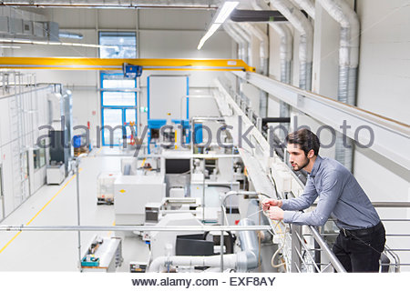 Male worker standing on balcony at tool manufacturing plant - Stock Photo